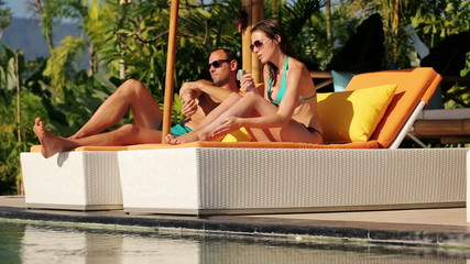 Couple on sunbeds applying sunscreen lotion on body by the pool