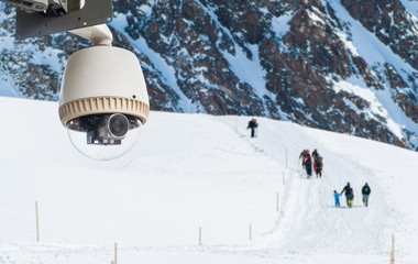 CCTV Camera Operating on snow mountain with people hiking in bac