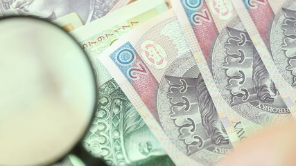 Full HD Polish zloty banknotes with magnifying glass