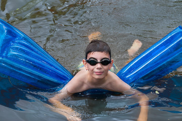 Boy swims on blue mattress in the river