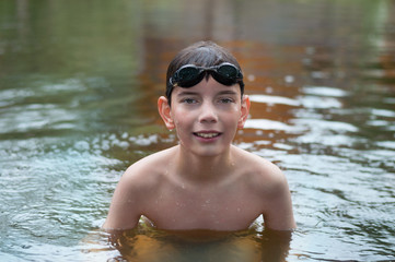 Boy with glasses in the river