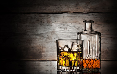 Glass of whiskey with ice cubes and faceted bottle