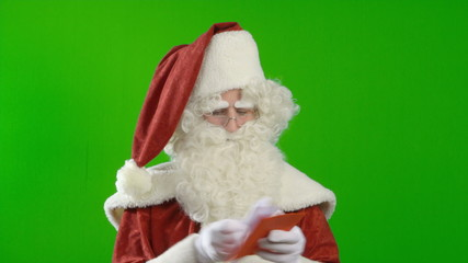 Santa Claus is reading a wish list and begins to laugh