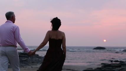 man with a woman walk along the beach