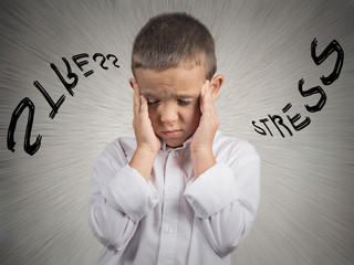 Stressed child having headache, isolated on grey wall background