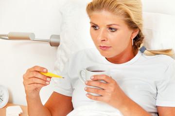 Frau im Bett ist Krank und hat Fieberthermometer.