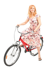 Mature lady posing seated on a bicycle