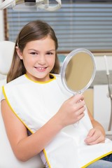 Little girl holding mirror in dentists chair