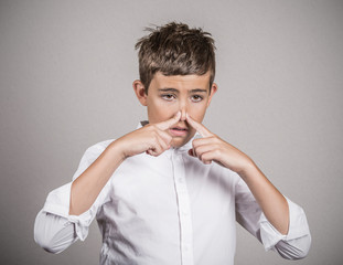 Teenager pinches his nose, bad smell, grey wall background