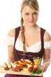 Frau im Dirndl mit traditionellem Essen
