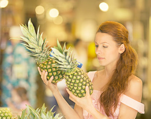 Woman shopping in supermarket, fruit section, freshness