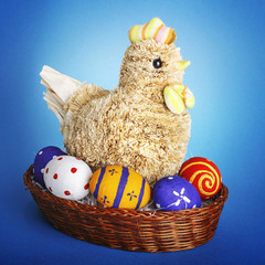 Handmade chicken wiht Easter eggs on blue background