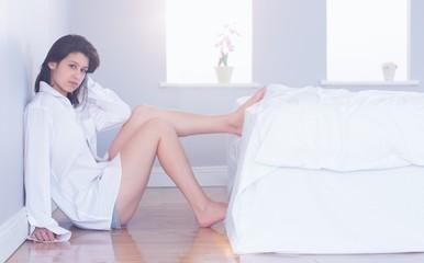 Sexy brunette sitting on floor beside bed