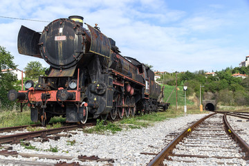 Ancient train with a steam locomotive on rails