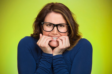 Anxious insecure woman isolated on green background