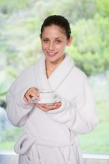 Beautiful woman in bathrobe having tea