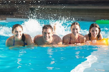 Cheerful people playing in the swimming pool