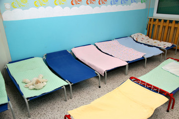 beds and cots in brightly colored dormitory of a nursery