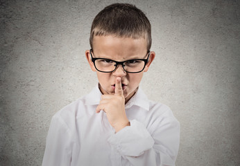 Boy giving be quiet gesture with finger on lips, grey background