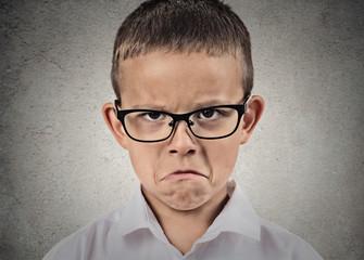 Unhappy sad, grumpy boy with glasses, grey wall background