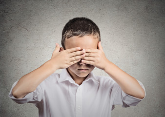 Boy covers his eyes with hands. See no evil concept