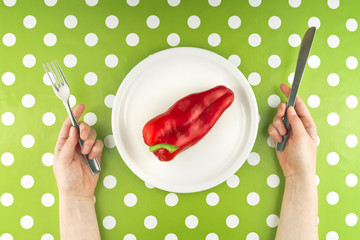 Woman eating raw red pepper, top view