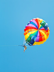 girl parakiting on parachute in blue sky