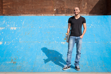 Skateboarder portrait standing on halfpipe at skate park.