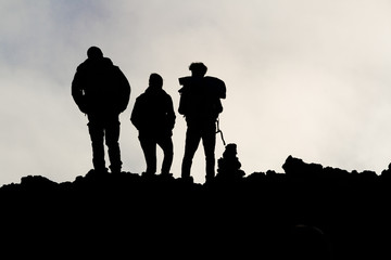 silhouettes of men on the volcano Etna