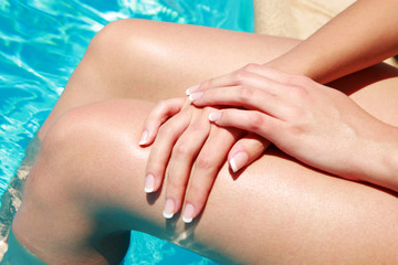 Closeup portrait of female legs with hands in swimming pool