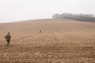 Gamekeepers walk over field in november fog.