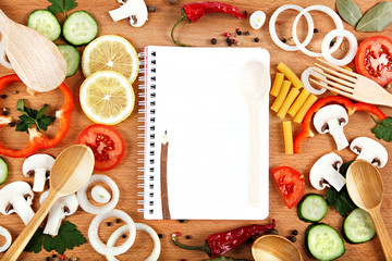 Vegetables, spices and recipes notepad on wooden cutting board.