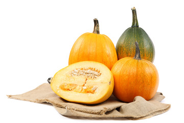 Pumpkins on sackcloth over white background.