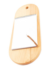 Notebook for recipes and pencil on wooden cutting board.