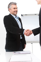 smiling people shaking hands in office.
