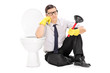 Sad man holding a plunger and sitting by a toilet
