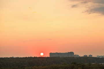 low red sun above horizon during sunrise over city
