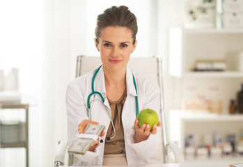 Doctor woman showing apple and pack of money