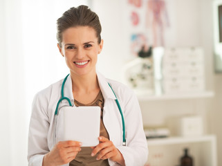 Happy doctor woman using tablet pc in office