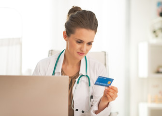 Doctor woman with credit card making online shopping