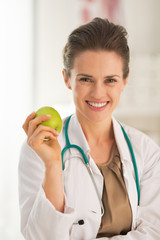 Portrait of smiling doctor woman with apple