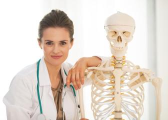 Portrait of doctor woman near human skeleton anatomical model