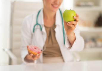 Closeup on doctor woman choosing between apple and donut