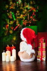 Pretty baby santa girl in angel wings with a gifts and xmas tree