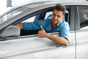 Car Showroom. Happy customer inside Car of His Dream.