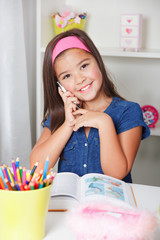 Beautiful young school girl talking on the phone while learning