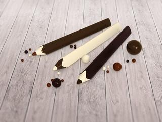 Chocolate pencils and balls on wooden floor