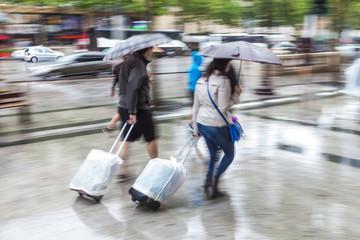 Paar mit Trolleys geht bei Regen in der Stadt