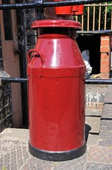 Old Retro red painted milk churn, Bridgnorth.