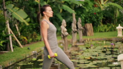 Young woman exercising, doing crouch with dumbbels in exotic gar